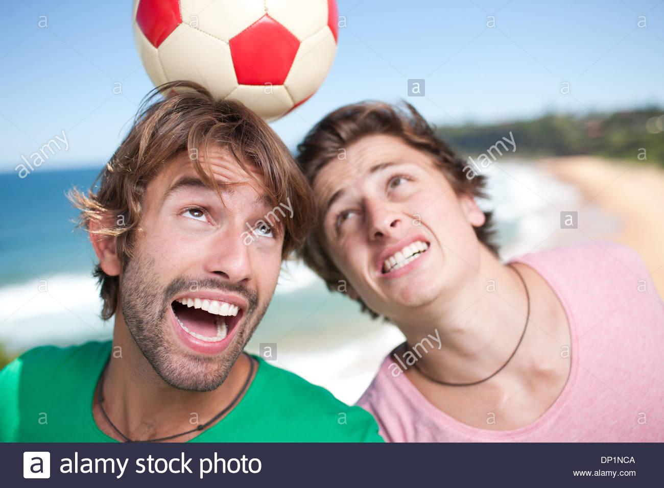 Les hommes jouent au soccer beach Photo Stock