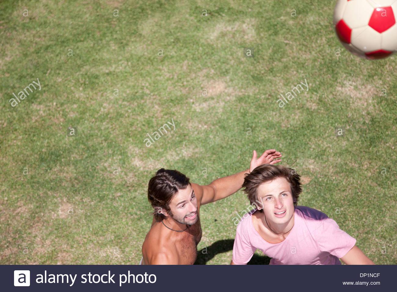 Les hommes jouant au football sur l'herbe Photo Stock
