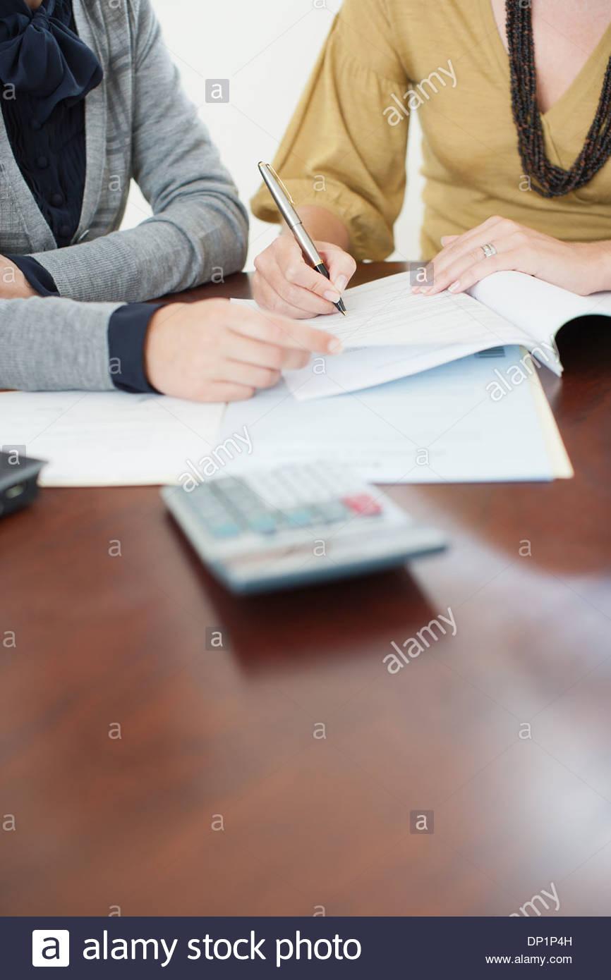 Portrait femme regardant signer la paperasse Photo Stock