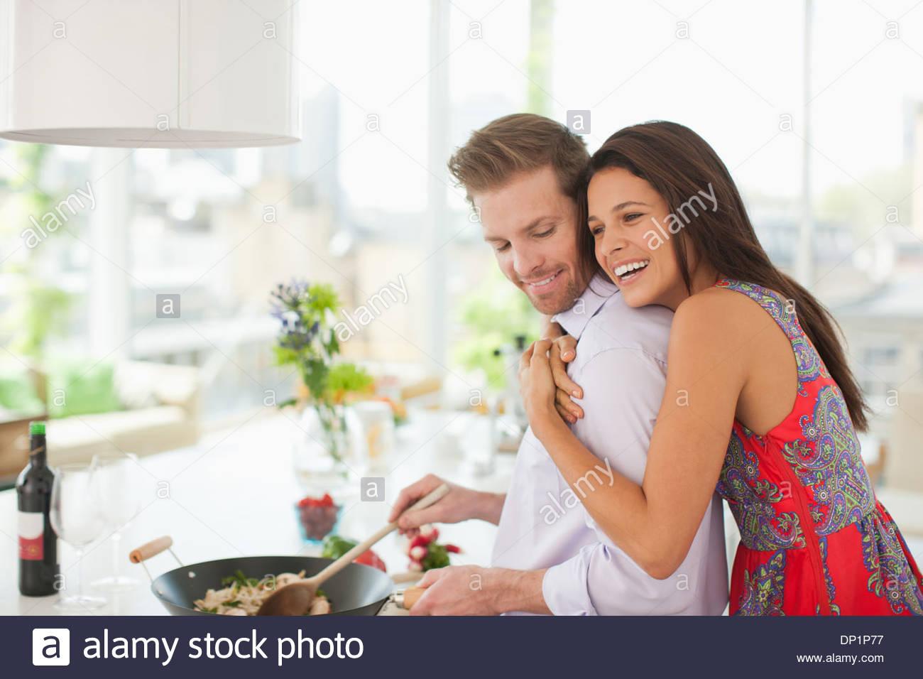 Woman hugging mari alors qu'il dans la cuisine la cuisine Photo Stock