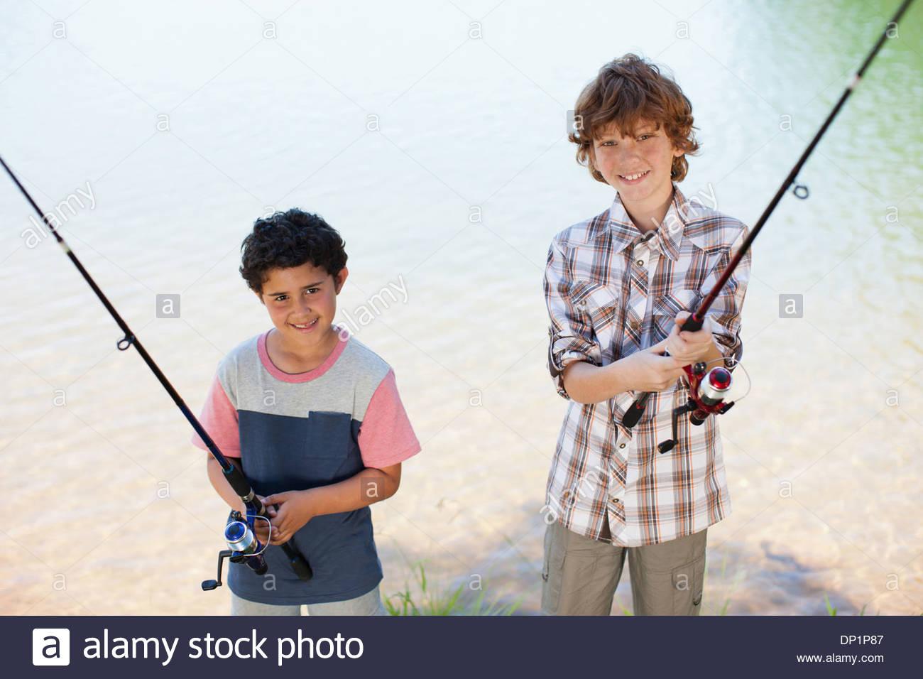 Les garçons tenant des cannes à pêche lakeside Photo Stock