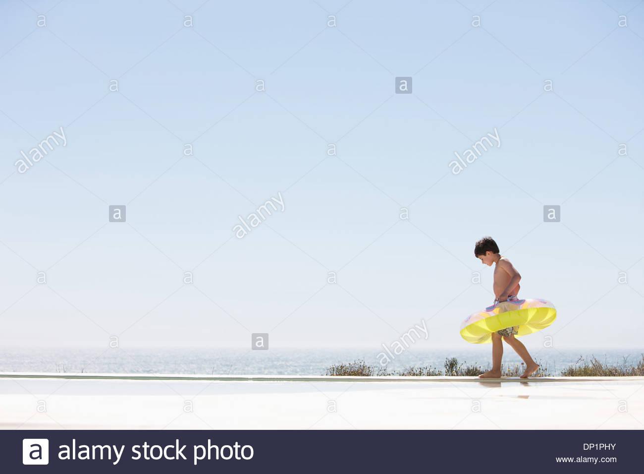 Garçon avec anneau gonflable faisant un pas hors de la piscine à débordement Photo Stock