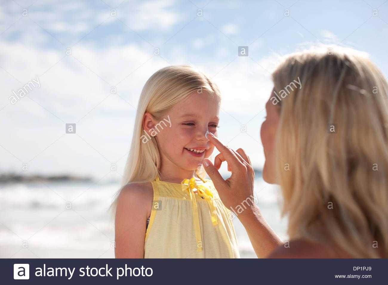 Appliquez un écran solaire à la mère le nez de la Fille Photo Stock