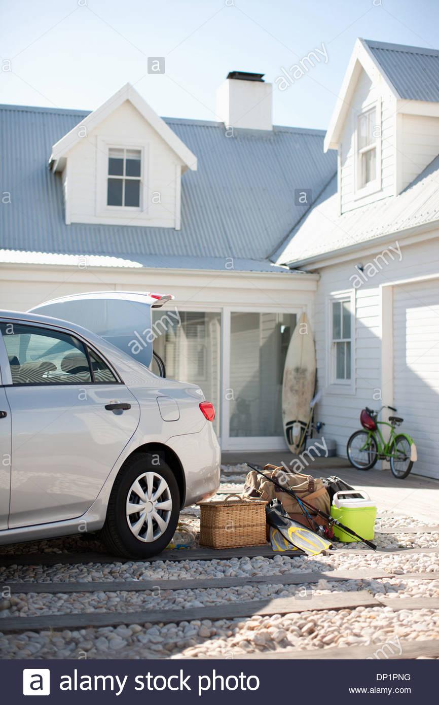 Panier à pique-nique, canne à pêche, palmes et sacs à l'extérieur de l'entrée en voiture Photo Stock