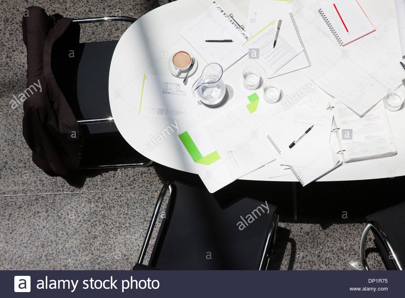 Directement au-dessus de la paperasse, du café, des ordinateurs portables et notebooks on conference table Photo Stock