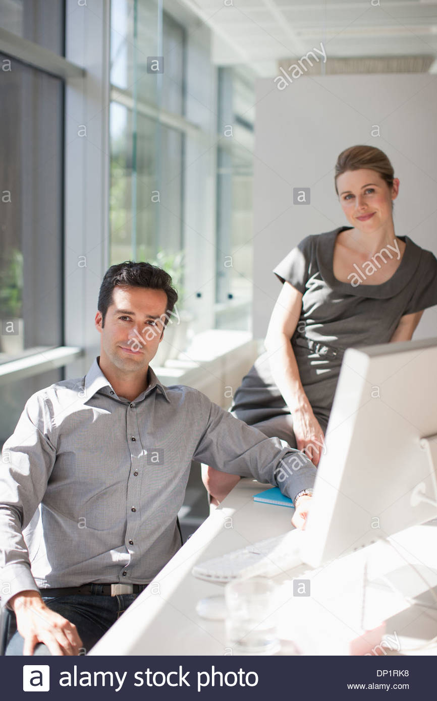 Businessman and businesswoman at computer in office Photo Stock