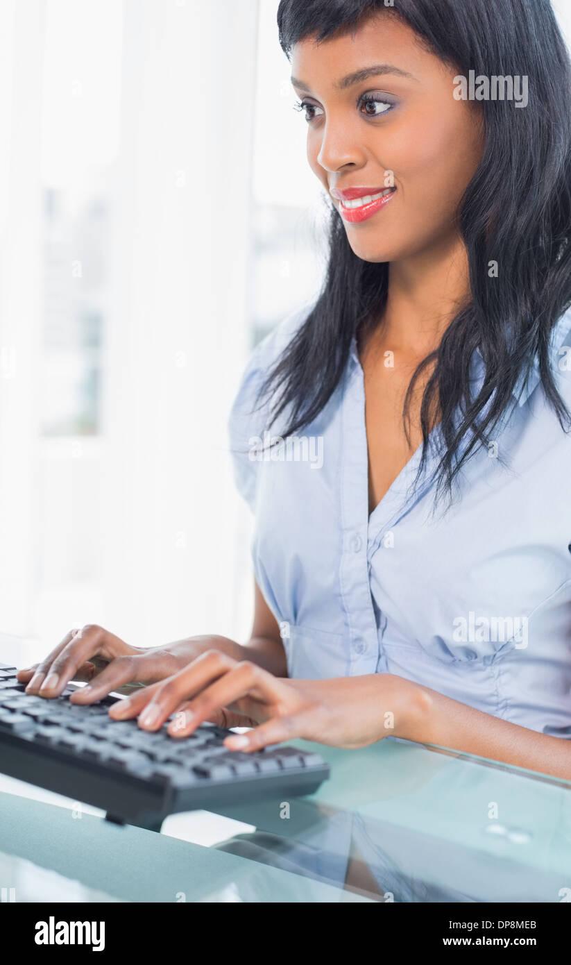 Smiling businesswoman la saisie sur un clavier Banque D'Images