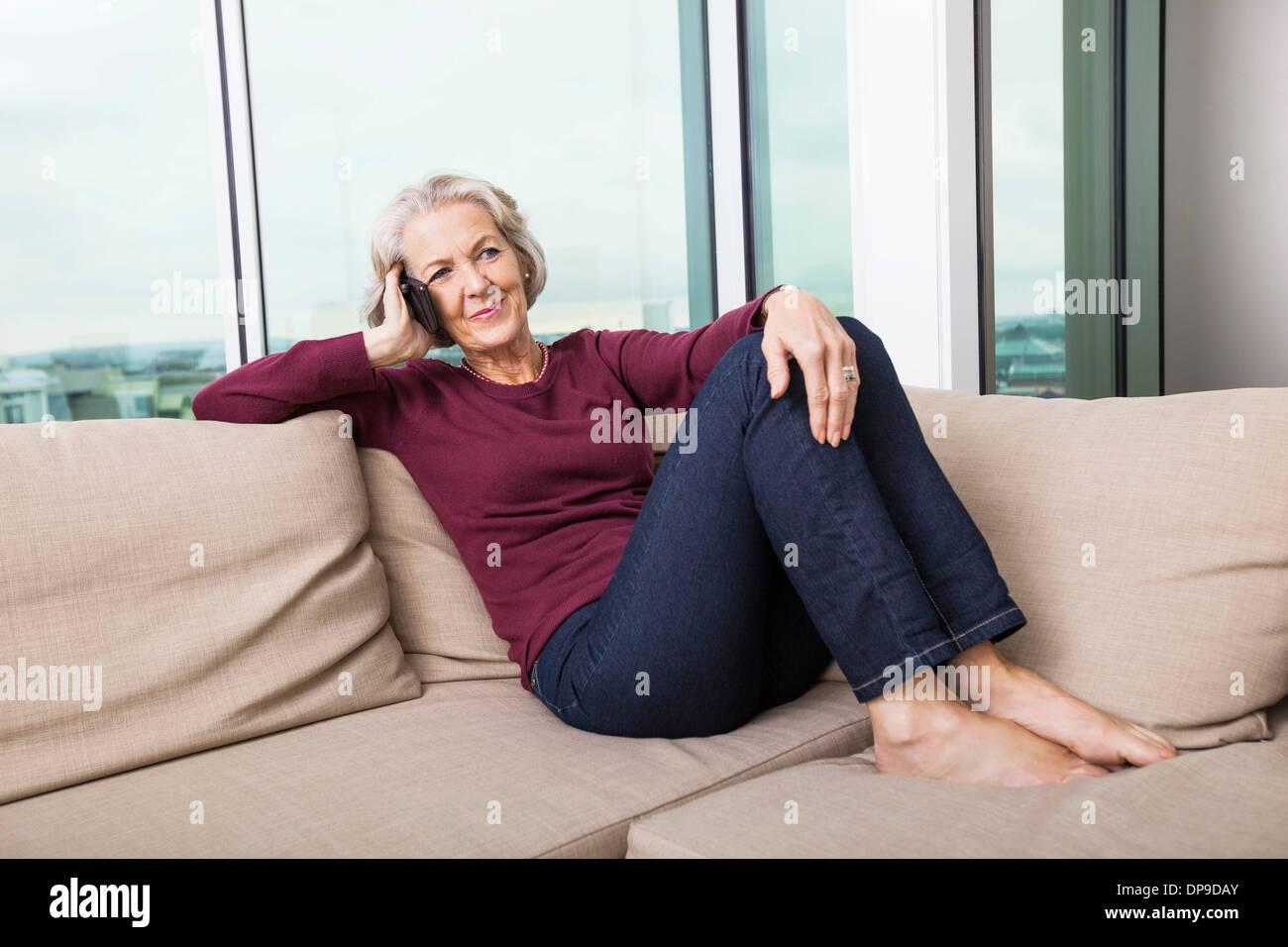 Full-length of senior woman répondre à smart phone on sofa at home Photo Stock