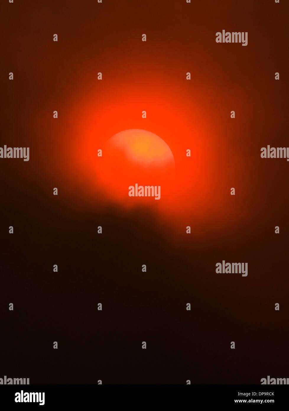 La fumée des feux de forêts crée une étrange lueur orange inhabituelle pour le coucher de soleil. Photo Stock