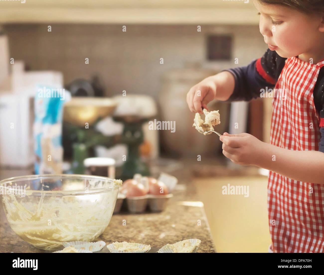 Enfant tenant une cuillère avec un mélange à gâteau Banque D'Images