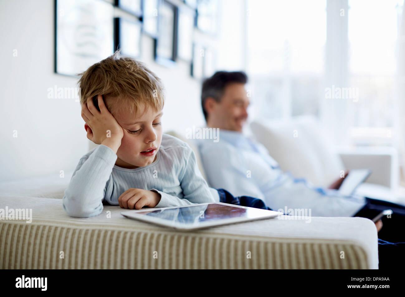 Père et fils sitting on sofa using digital tablets Banque D'Images