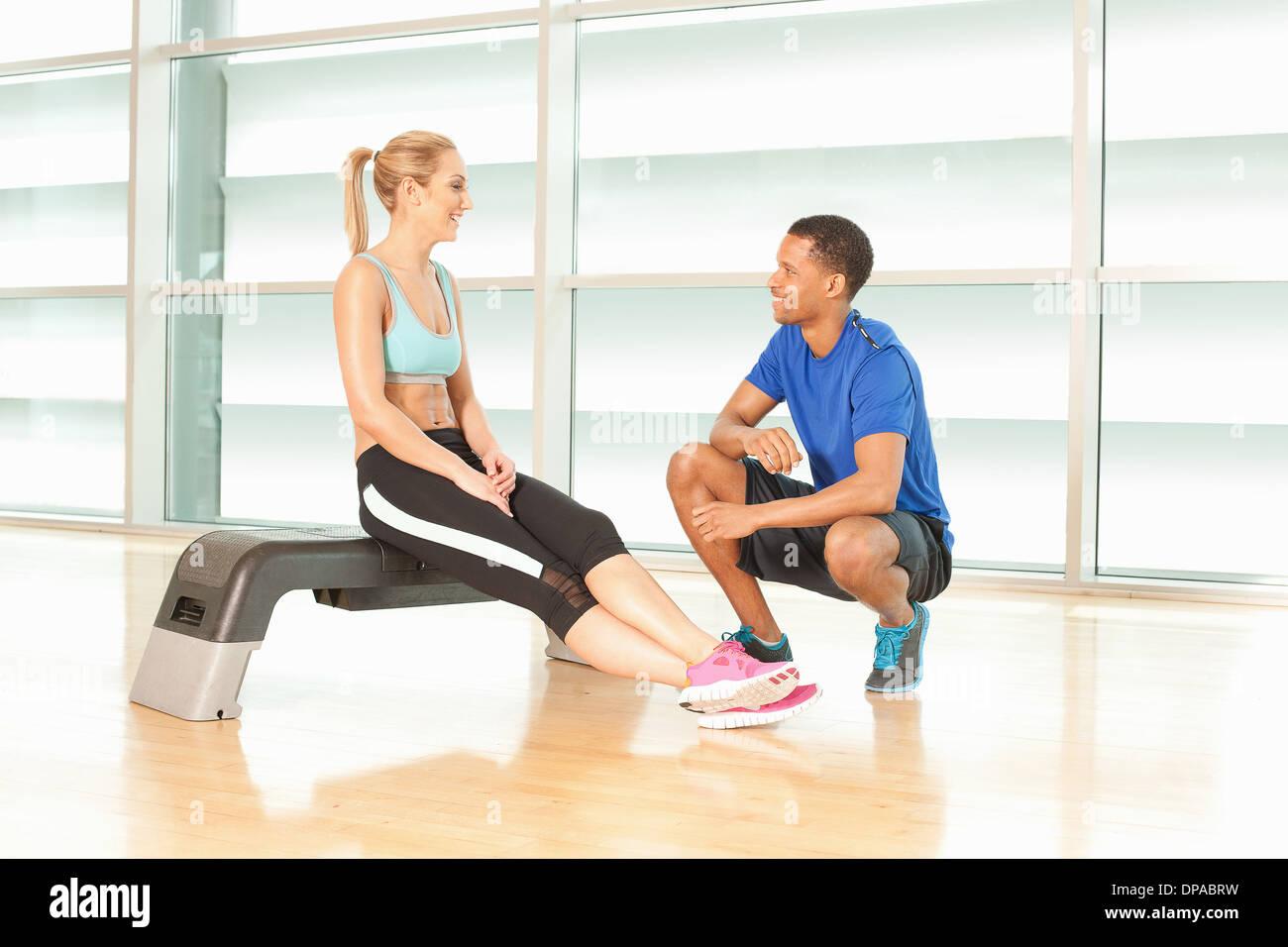 Femme assise sur l'étape de l'exercice de parler à l'instructeur de conditionnement physique Photo Stock
