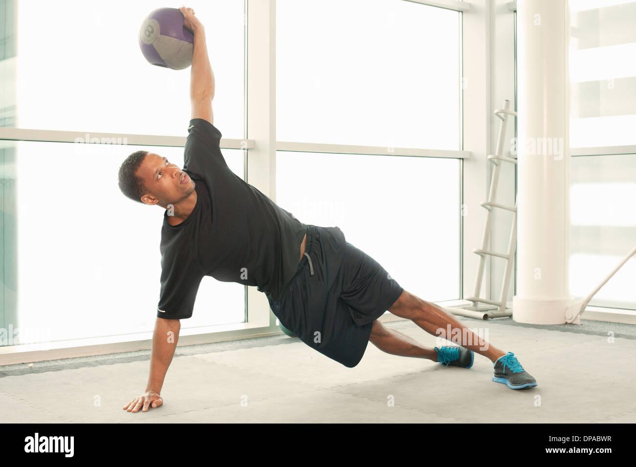 L'homme s'étend à l'aide de boule d'exercice Photo Stock