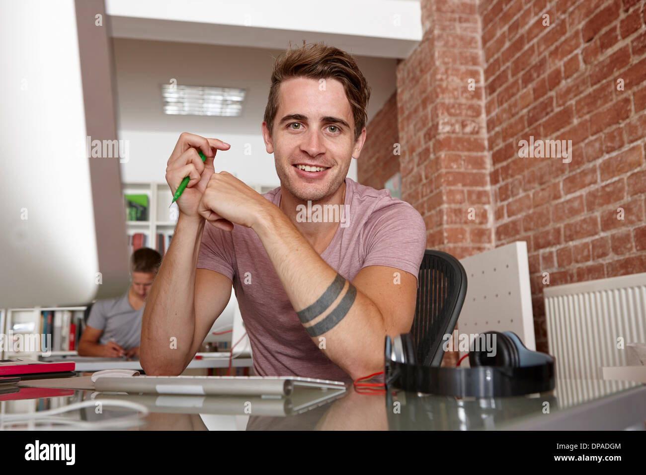 Portrait of young man at desk Photo Stock