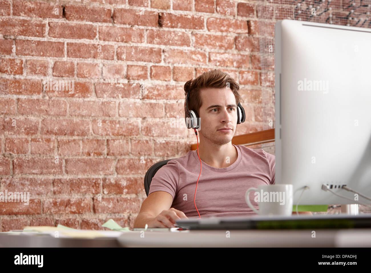 Jeune homme à l'aide d'ordinateur portant des écouteurs Photo Stock