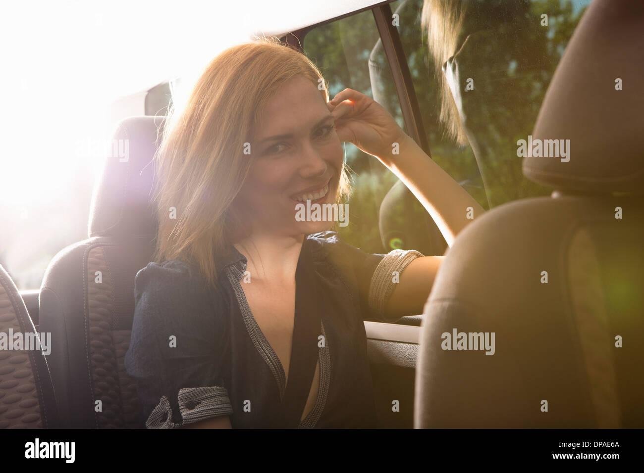 Jeune femme voyageant au siège arrière de voiture Photo Stock