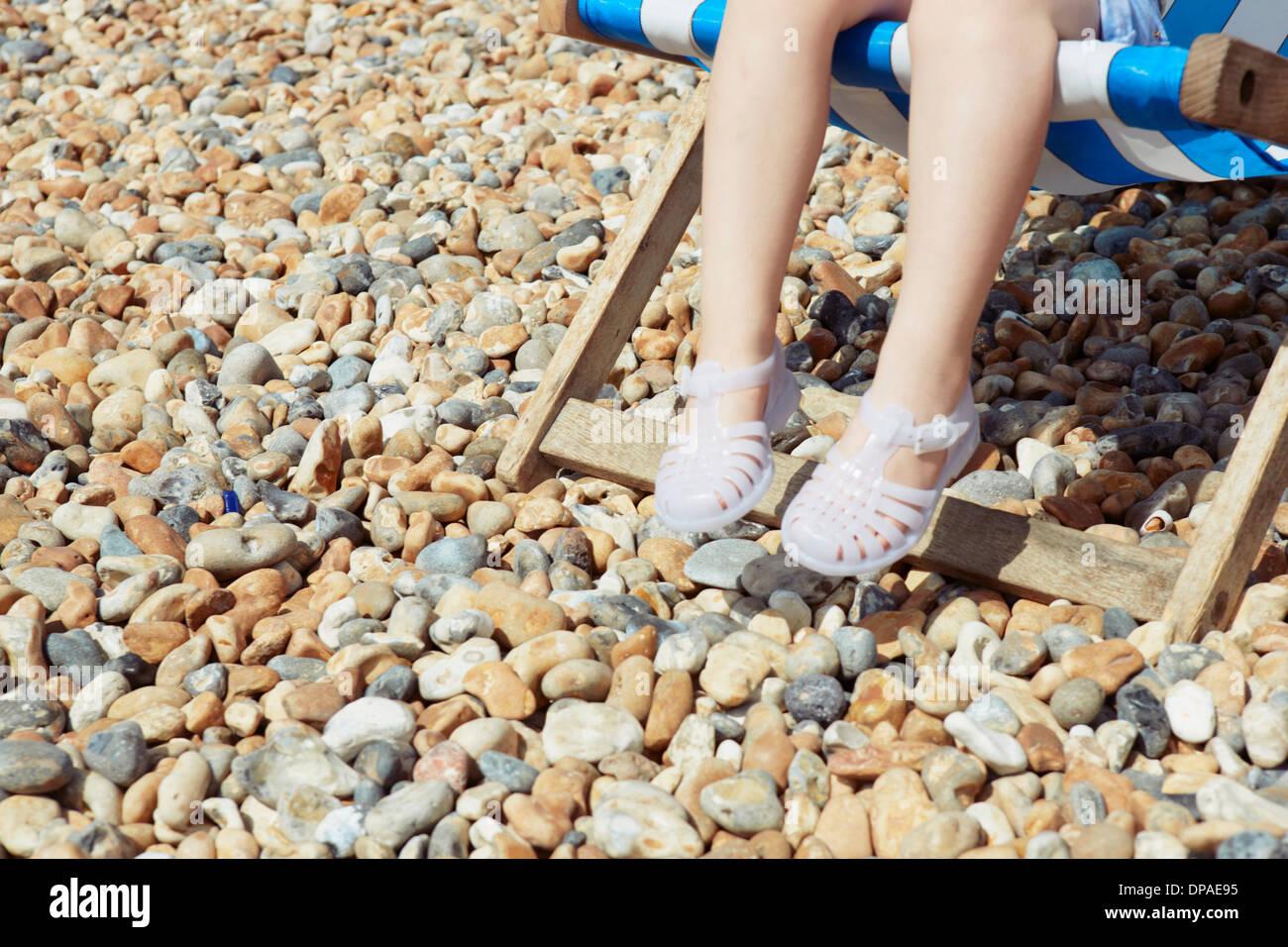 Enfant avec des sandales en plastique sur une chaise de plage Photo Stock