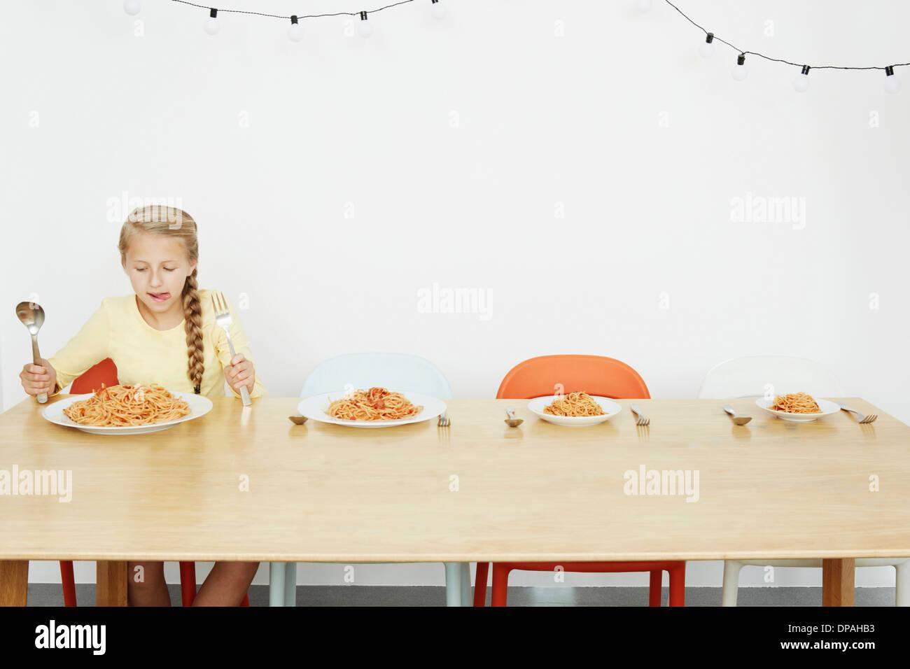 Fille assise à table avec trois plaques spaghetti et plus Photo Stock