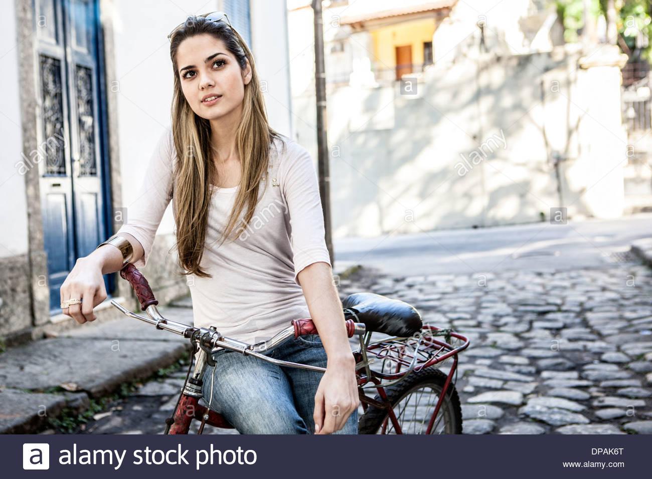 Jeune couple à bicyclette dans la rue pavée, Rio de Janeiro, Brésil Photo Stock