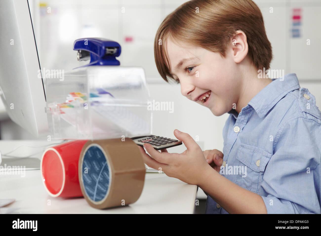 Garçon jouant avec l'équipement de bureau Photo Stock