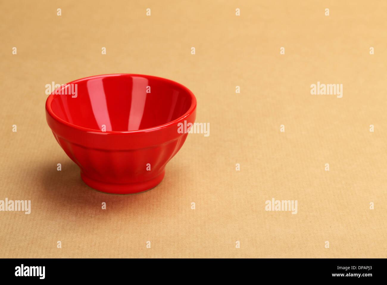 Un bol en céramique rouge vide sur fond de papier de l'emballage Photo Stock