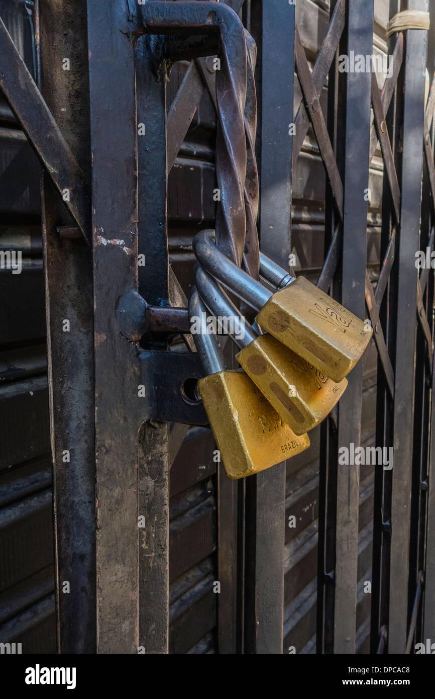 Plusieurs cadenas sécuriser une porte métallique coulissante du magasin à Sucre, Bolivie. Photo Stock
