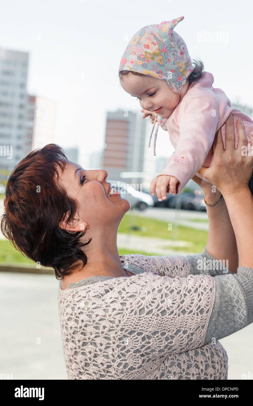 Portrait d'une mère heureuse en ville avec l'enfant sur les mains. Photo Stock