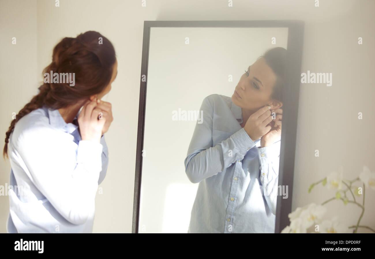 Belle femme mise sur son oreille dans l'avant du miroir. Man s'habiller pour le travail. Modèle des femmes de race Banque D'Images