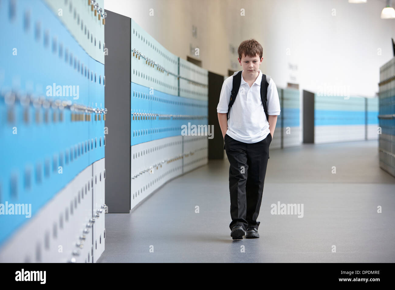 Écolier malheureux de marcher seul dans les couloir d'école Photo Stock