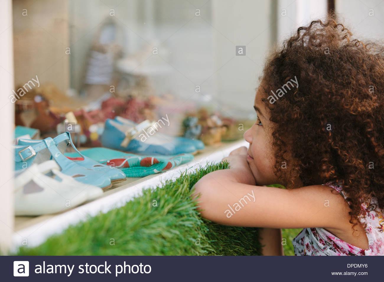 Jeune fille à la fenêtre du magasin de chaussures par Photo Stock