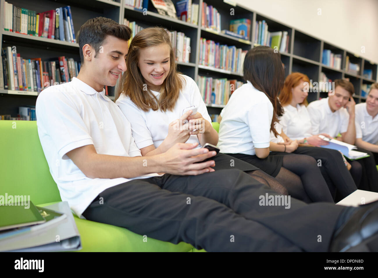 Rangée d'adolescents hanging out in library Photo Stock