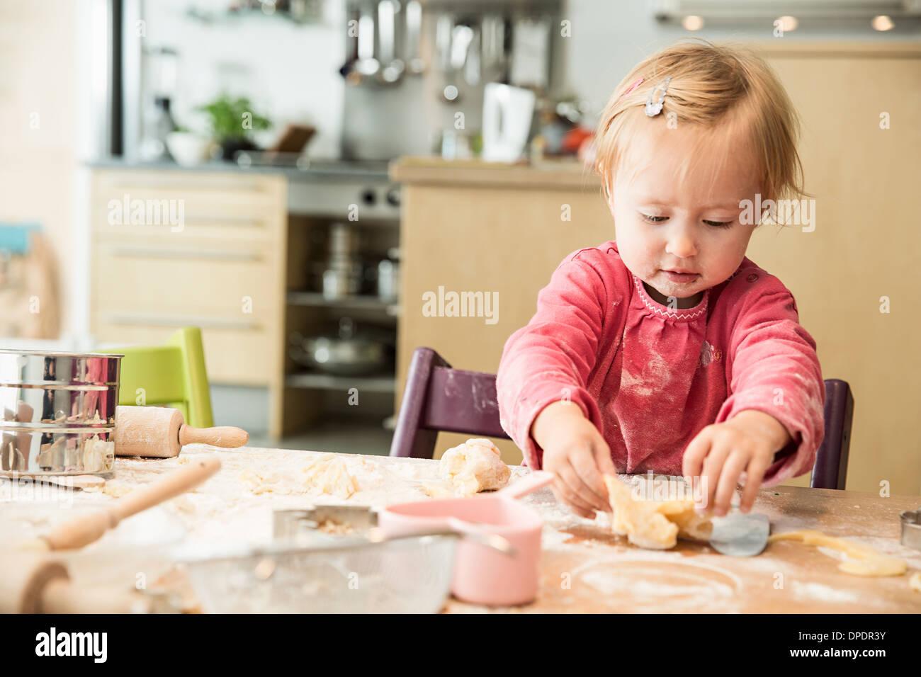 Baby Girl baking in kitchen Photo Stock