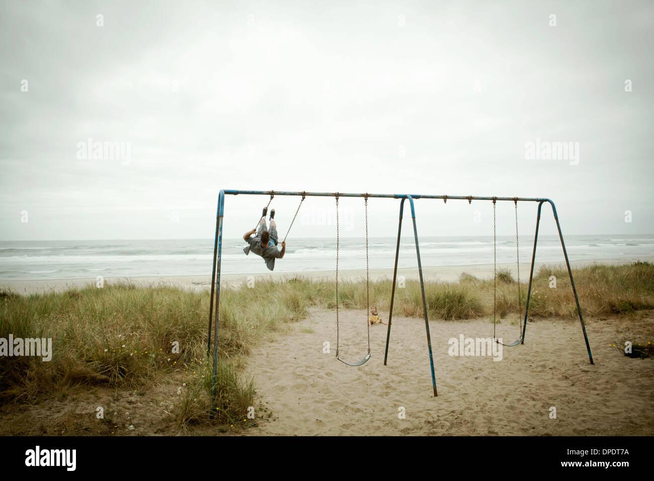Female toddler watching father on beach swing Photo Stock
