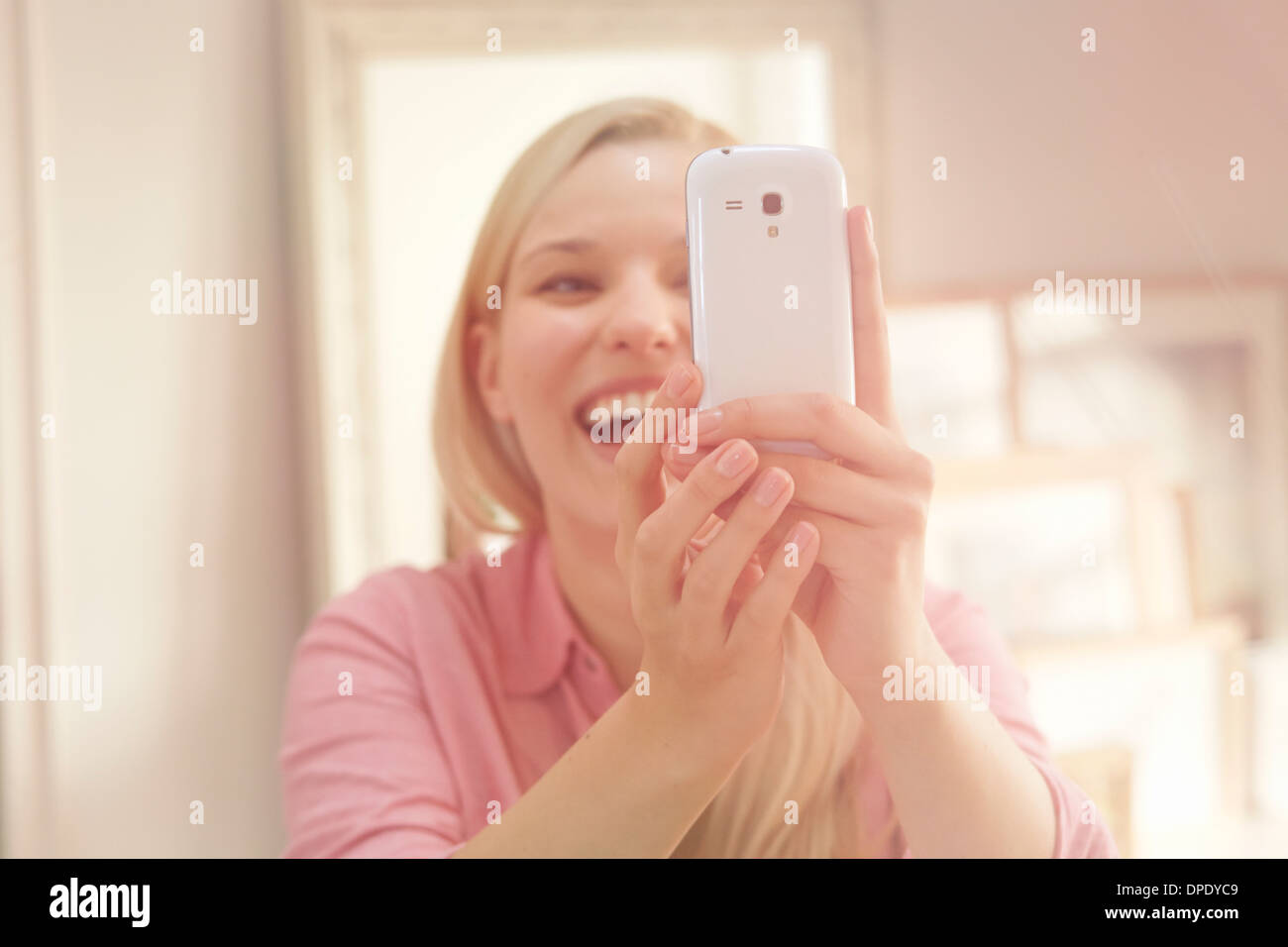 Young woman taking self portrait photograph using smartphone Photo Stock