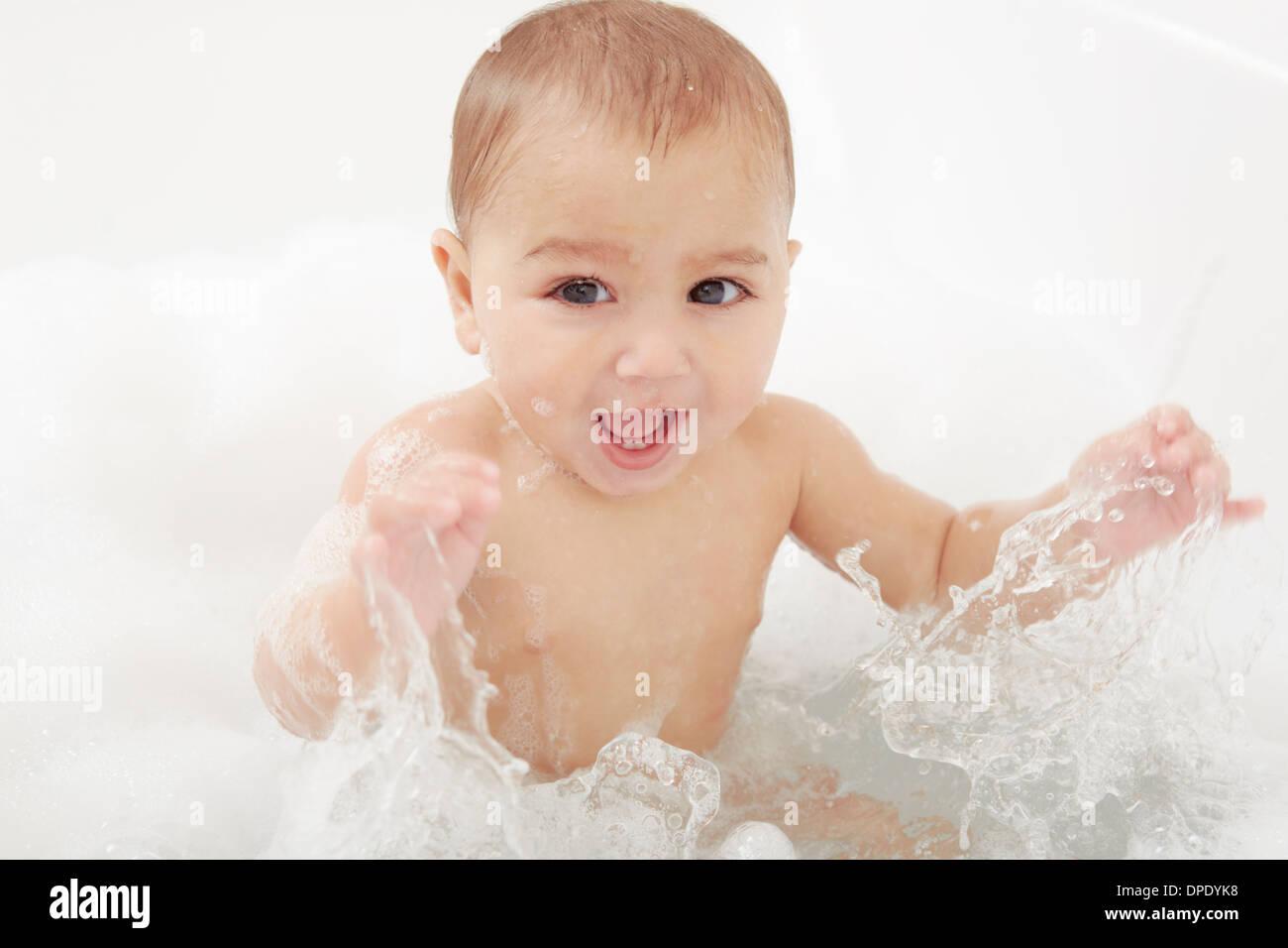 S'éclabousser dans une baignoire de bébé Photo Stock
