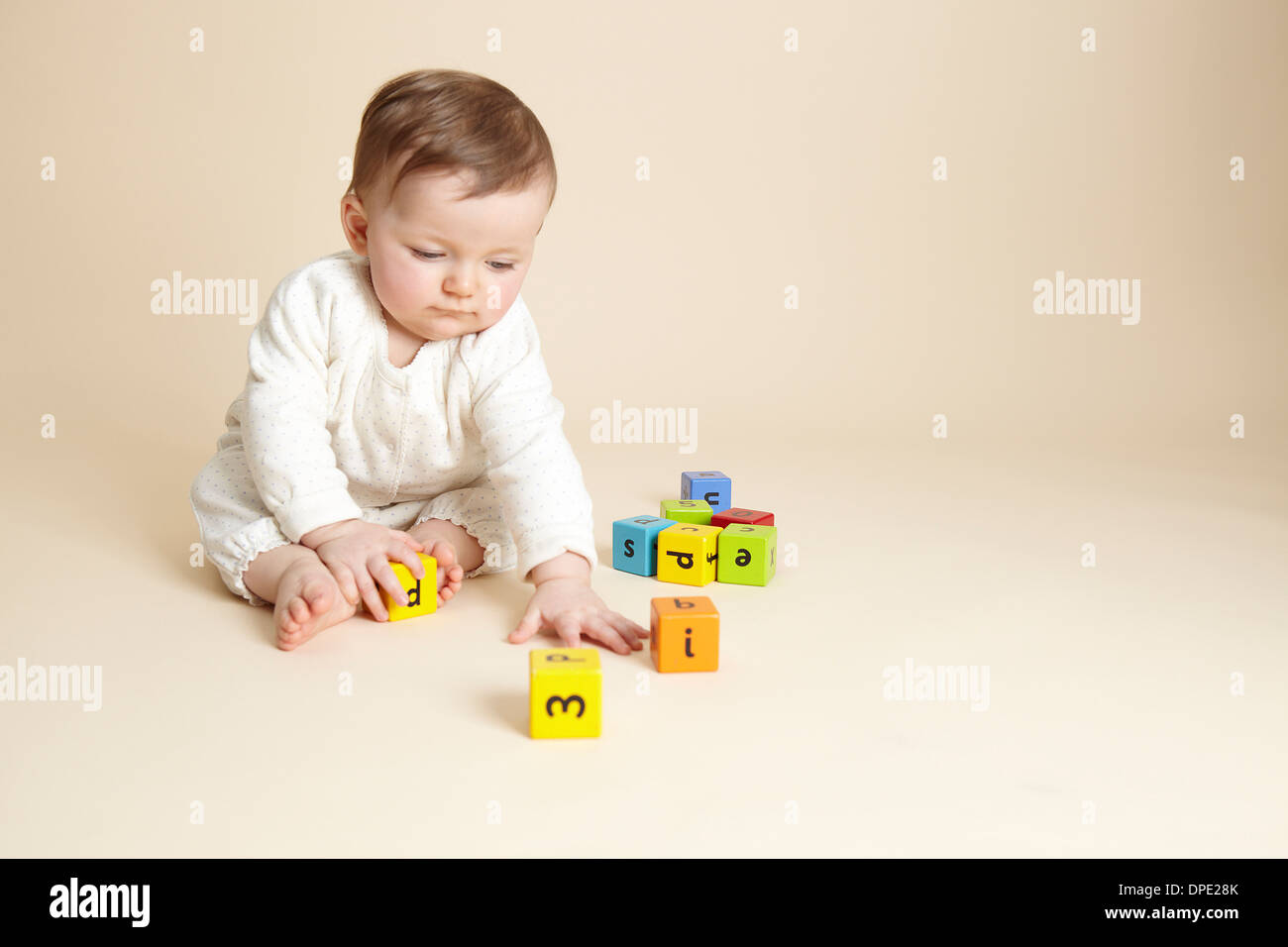 Studio portrait of baby girl Playing with alphabet blocks Photo Stock