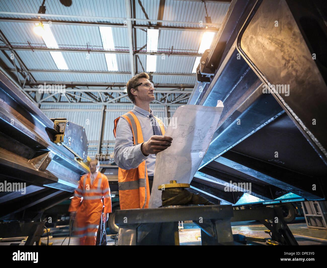 Ingénieur avec dessins techniques en usine Photo Stock