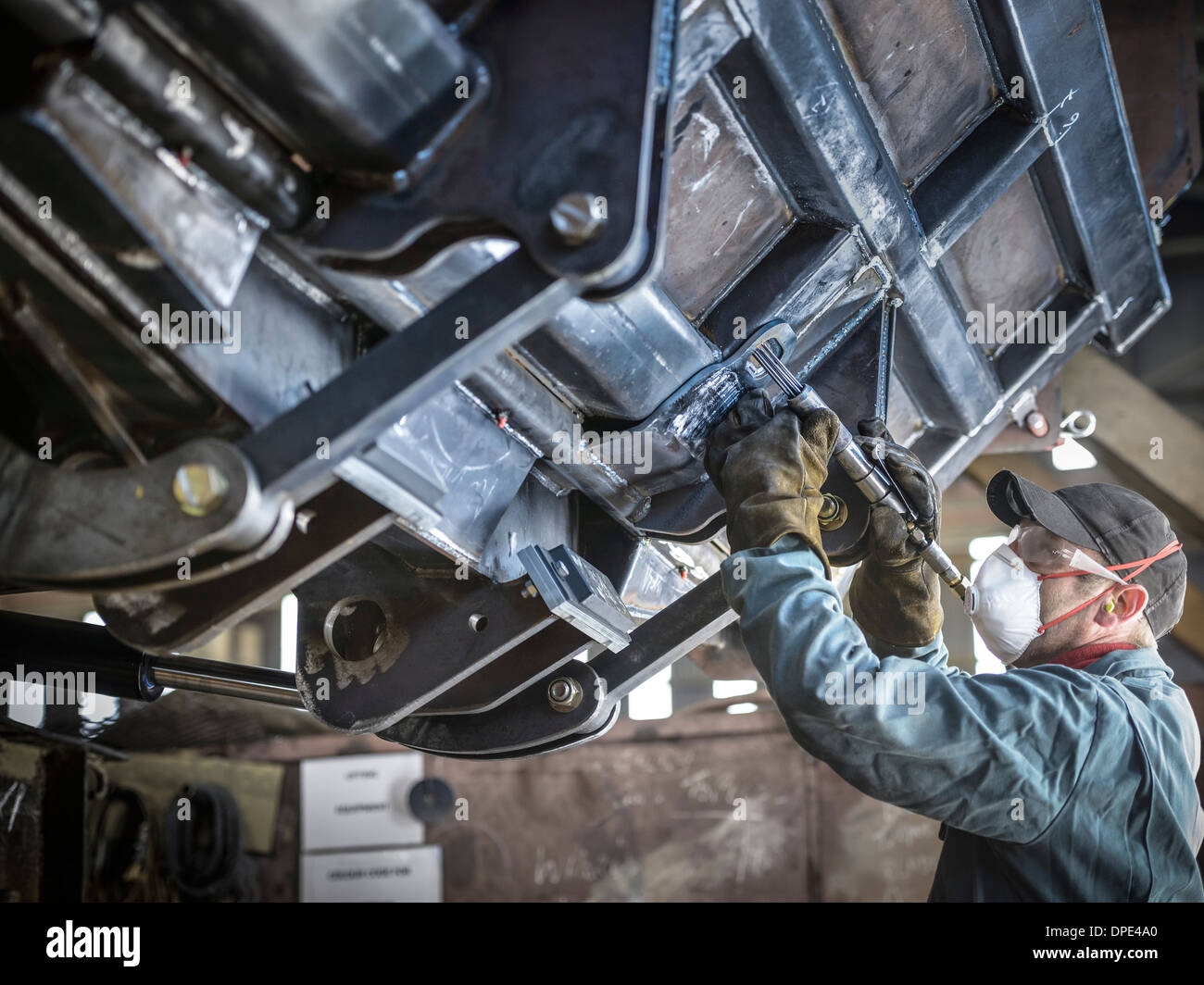 Engineer smoothing welds in factory Banque D'Images
