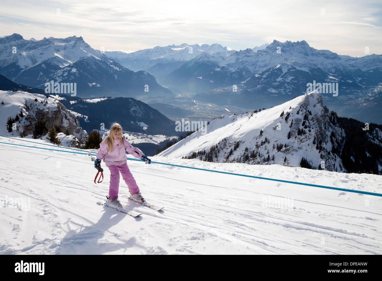 Un jeune enfant le ski, à l'aide d'un téléski de ne pas porter un casque de ski, swiss alps, Switzerland, Europe Photo Stock