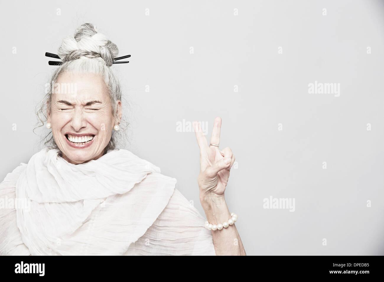 Studio portrait of senior woman sophistiquées faisant signe de victoire Photo Stock