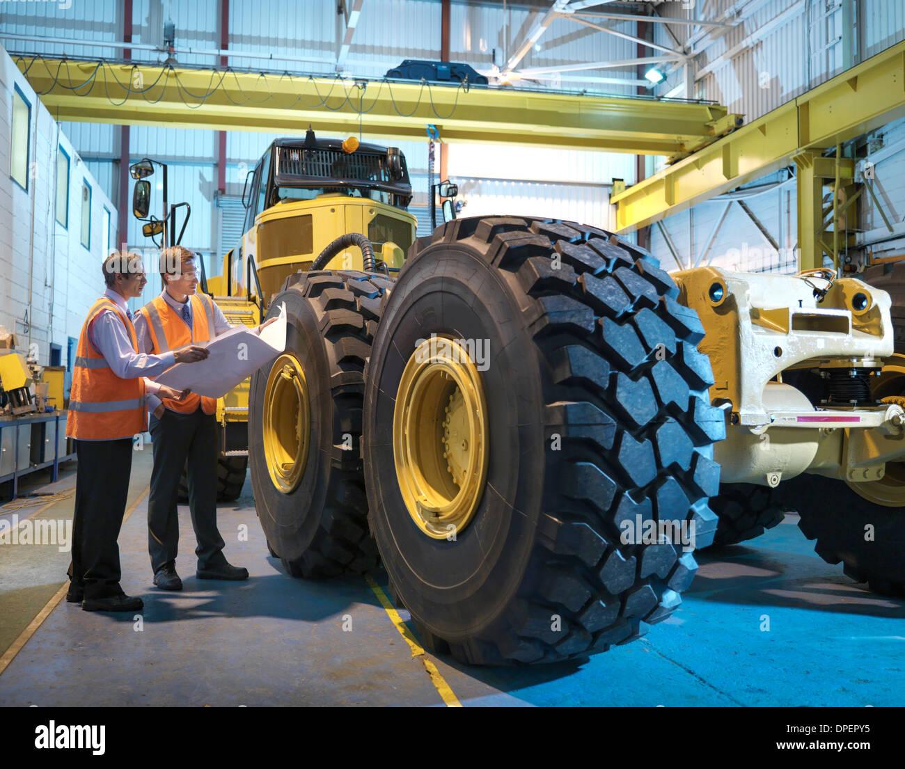 Des dessins d'ingénierie les ingénieurs avec l'inspection de véhicule lourd Photo Stock