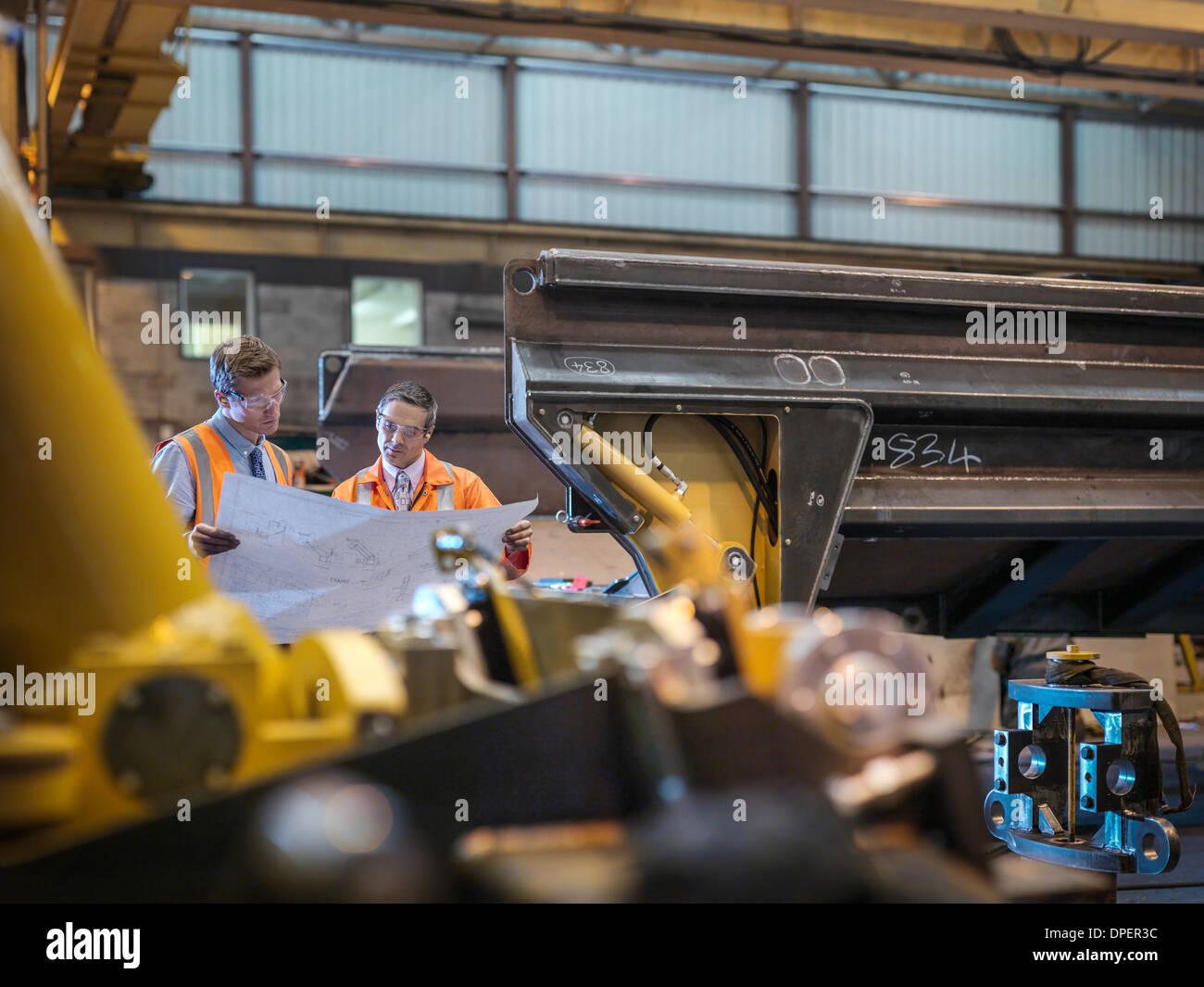 Engineers inspecting engineering drawings ensemble en usine Photo Stock