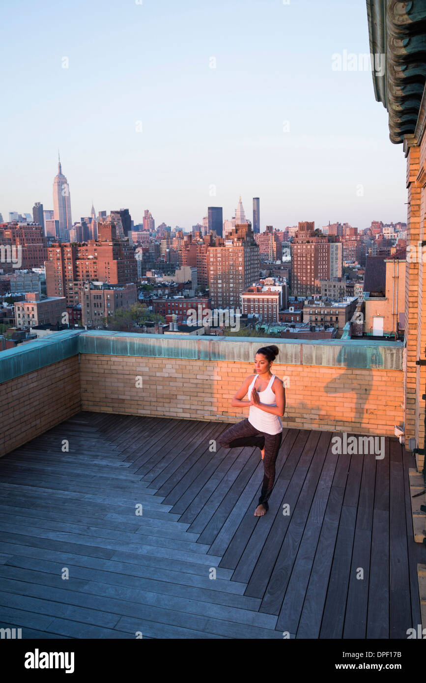 Woman practicing yoga on rooftop Photo Stock