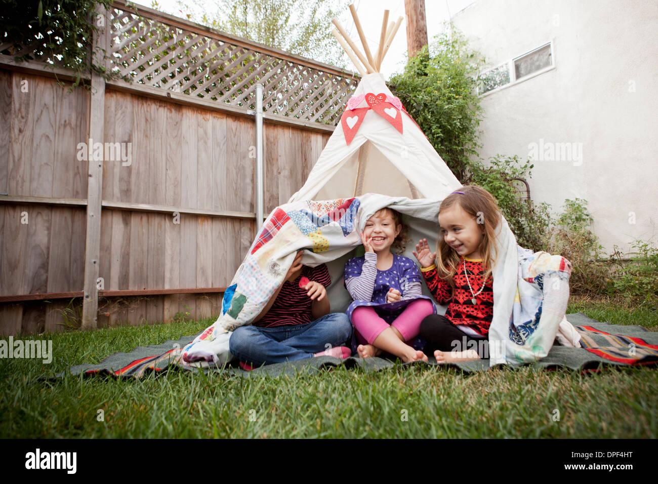 Trois jeunes filles dans le jardin caché sous couverture Photo Stock
