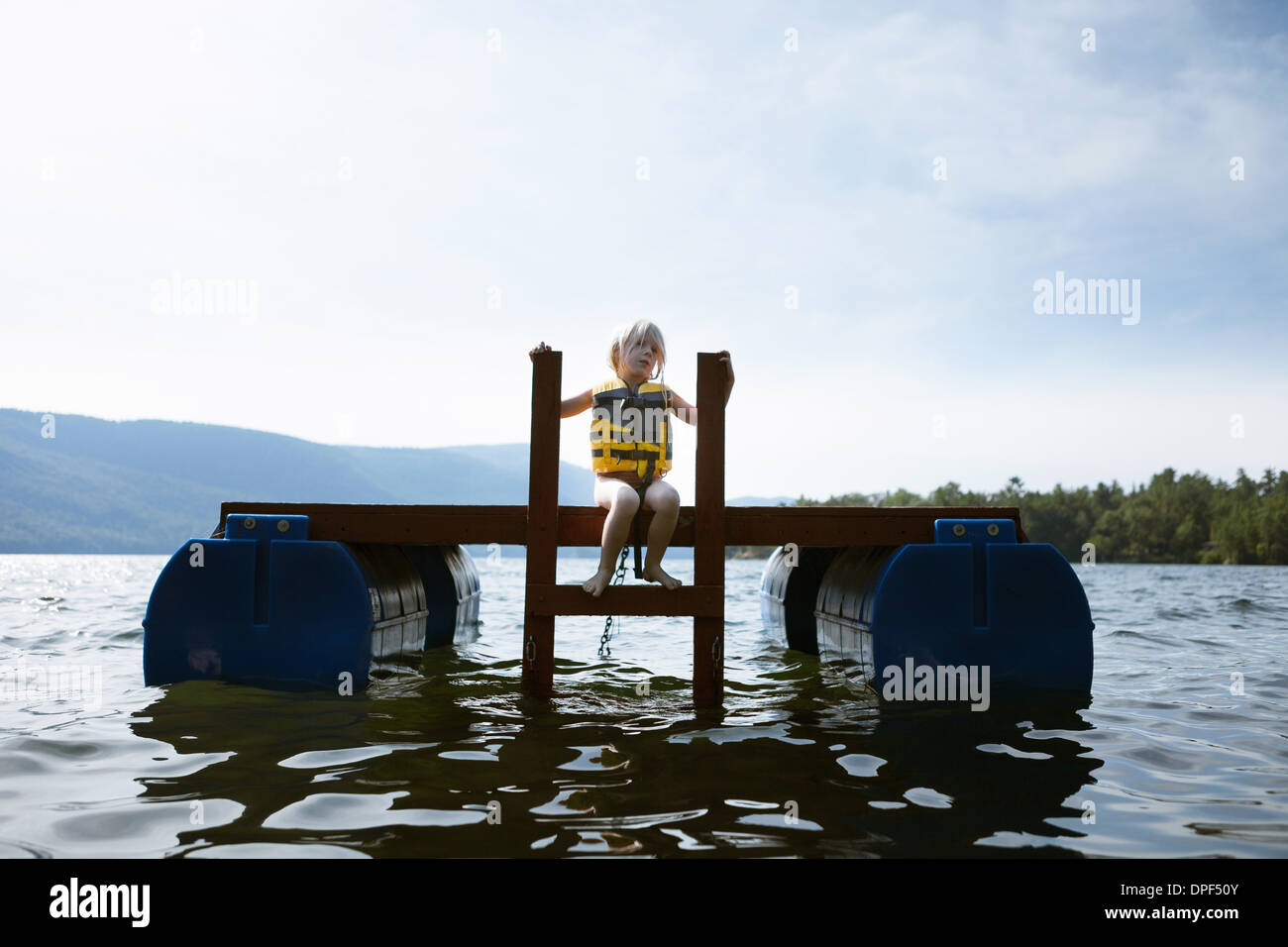 Female toddler sitting sur plate-forme flottante, Silver Bay, New York, USA Photo Stock