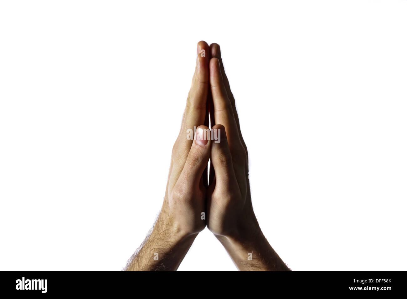 Mains jointes pour une prière isolé sur fond blanc Photo Stock