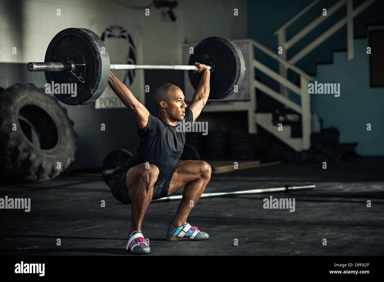 Jeune homme haltérophilie barbells in gymnasium Photo Stock