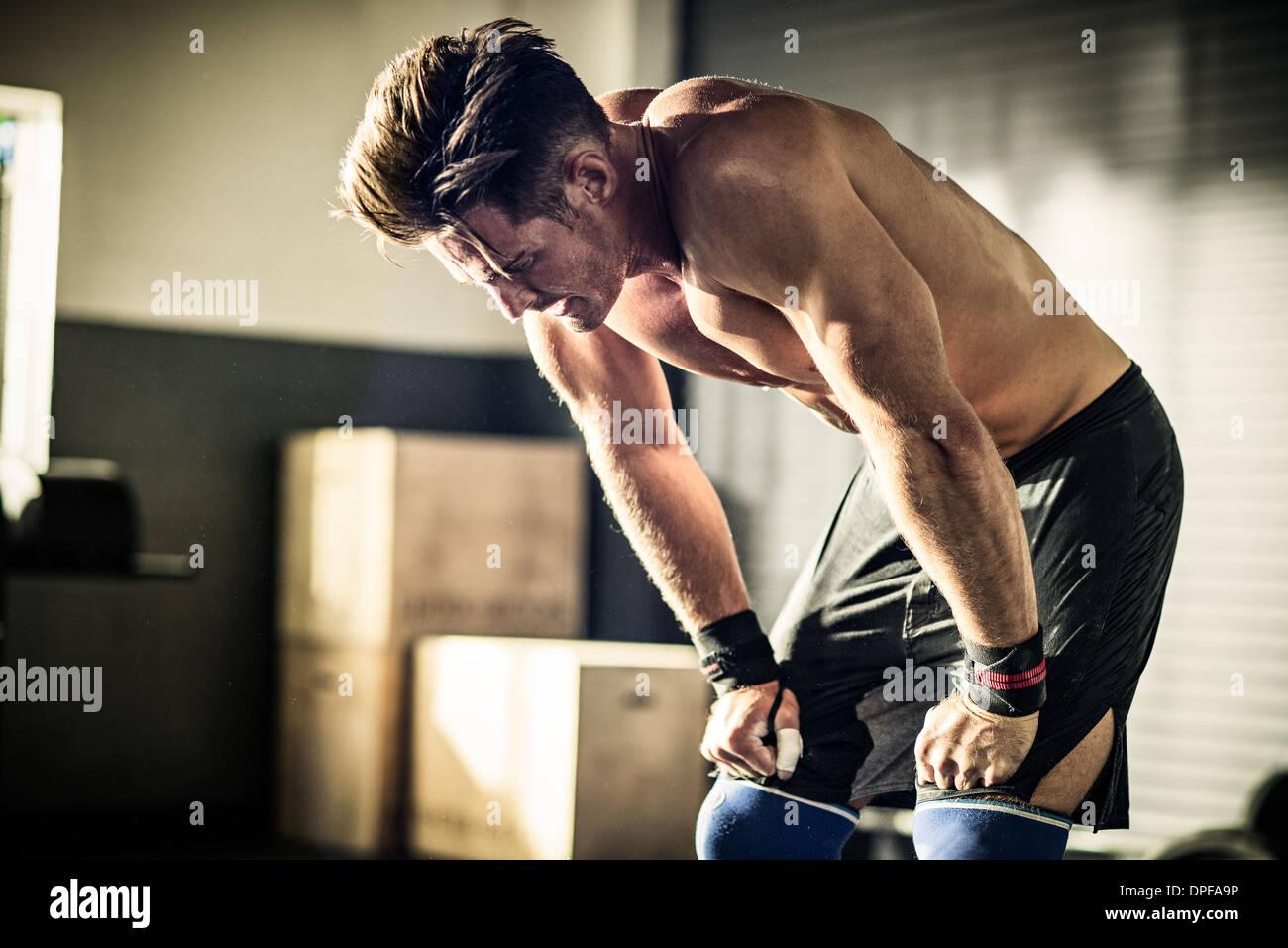 Jeune homme se pencher vers l'avant avec l'épuisement in gymnasium Photo Stock