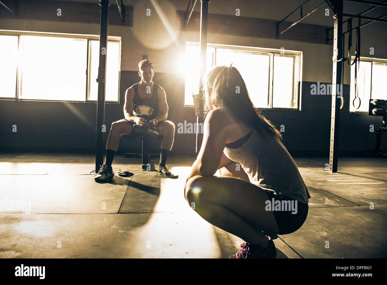 Formateur femelle mâle mentorat client dans un gymnase Photo Stock