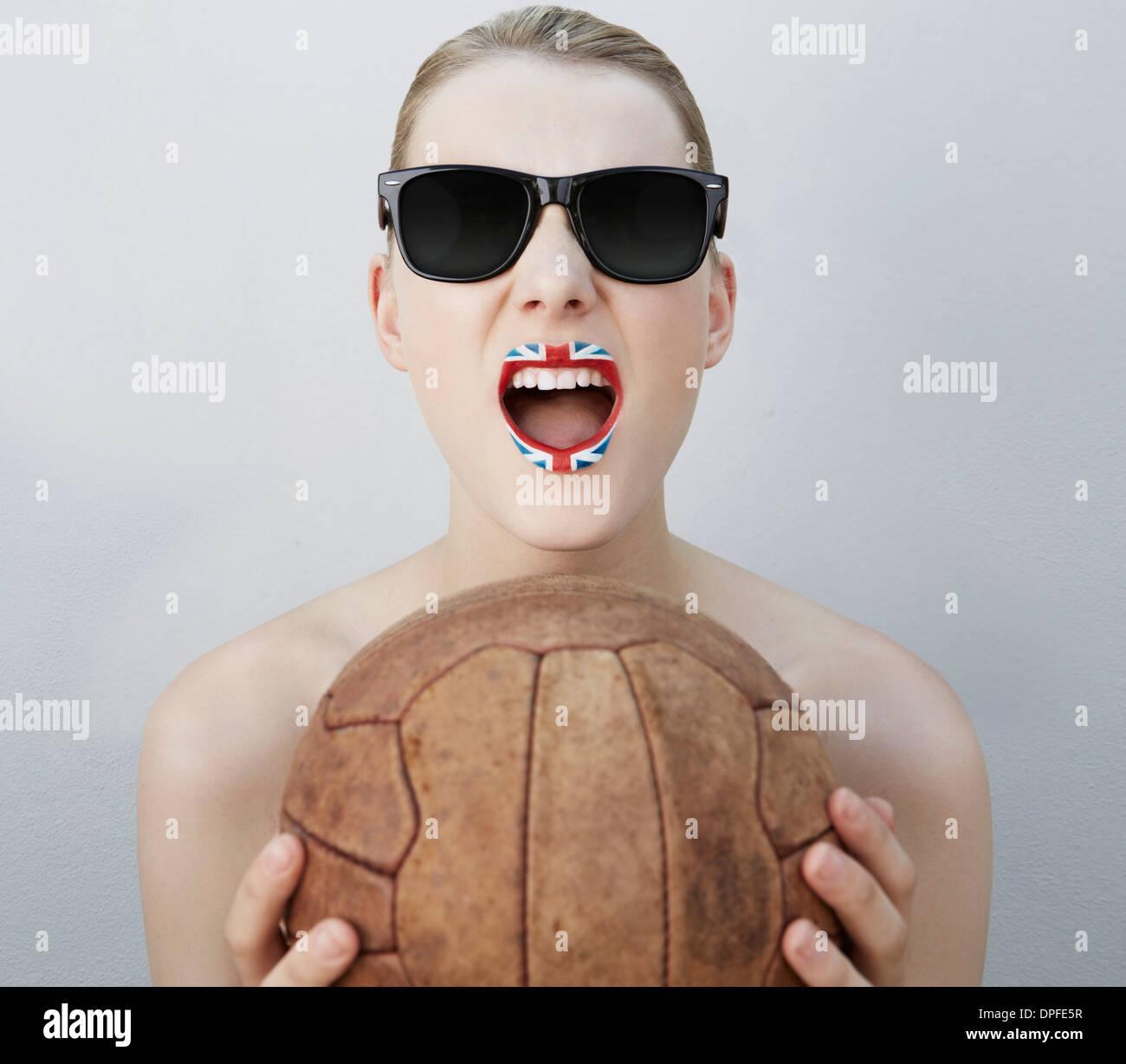 Femme avec drapeau britannique rouge à lèvres, holding soccer ball Photo Stock